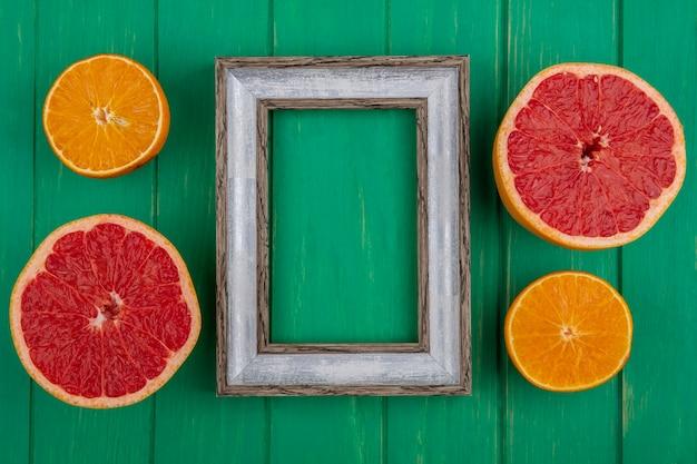 녹색 배경에 자몽과 오렌지의 절반과 상위 뷰 복사 공간 회색 프레임