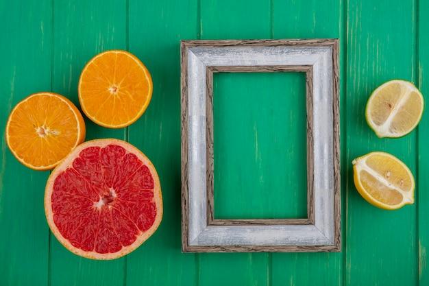 자몽 라임 레몬과 오렌지 녹색 배경에 절반 상위 뷰 복사 공간 회색 프레임