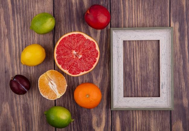 레몬 라임 오렌지와 나무 배경에 절반 자몽 상위 뷰 복사 공간 회색 프레임
