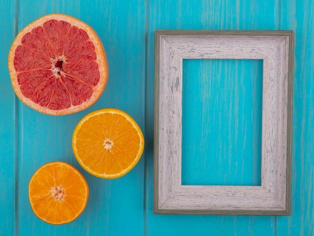 Vista dall'alto copia spazio cornice grigia con fetta d'arancia e fetta di pompelmo su sfondo turchese