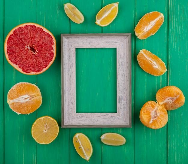 껍질을 벗긴 오렌지와 레몬 라임과 녹색 배경에 절반 자몽 슬라이스 상위 뷰 복사 공간 회색 프레임