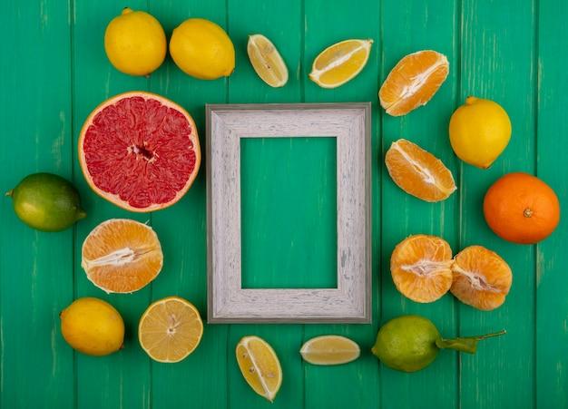 皮をむいたオレンジとレモンライムと緑の背景に半分のグレープフルーツスライスと上面コピースペース灰色のフレーム