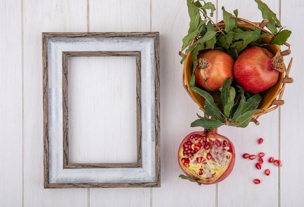 Top view  copy space gray frame with pomegranates and branches of leaves in basket on white background