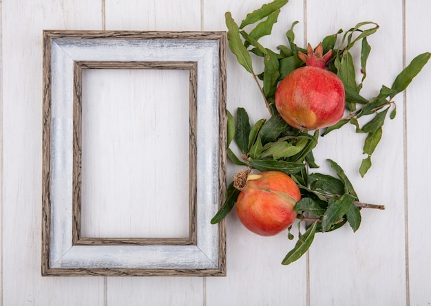 Top view  copy space gray frame with pomegranates and branches of leaves on white background