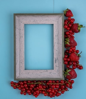 Top view copy space gray frame with strawberries and red currants on a light blue background