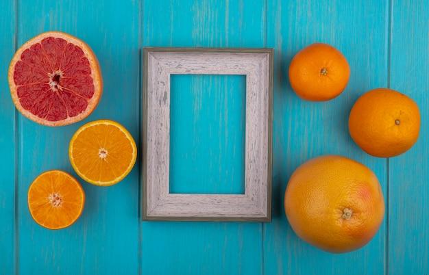 청록색 배경에 웨지와 전체 오렌지와 자몽 상위 뷰 복사 공간 회색 프레임