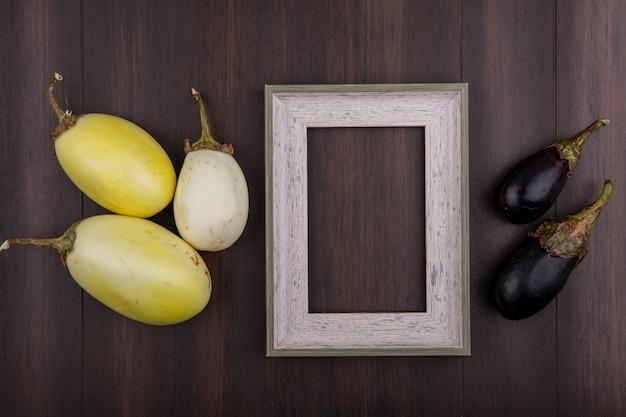Vista dall'alto copia spazio cornice grigia con melanzane bianche e nere su fondo in legno