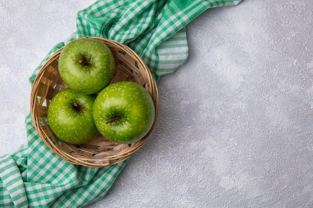 Vista dall'alto copia spazio nel carrello delle mele verdi sul tovagliolo a scacchi verde su sfondo bianco