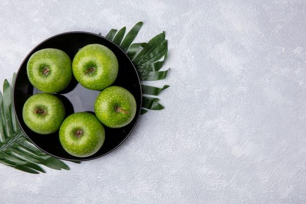 Vista dall'alto copia spazio mele verdi su un piatto nero sui rami con foglie su uno sfondo bianco
