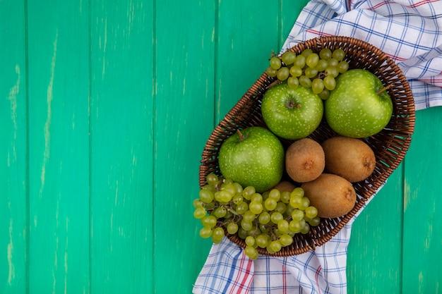 Вид сверху копией космических зеленых яблок с киви и виноградом в корзинах на клетчатом полотенце на зеленом фоне