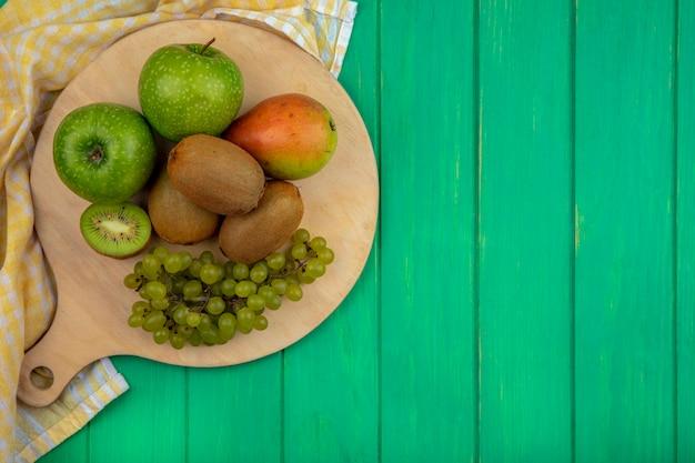 Top view copy space mele verdi con kiwi uva verde e pera su un supporto con un asciugamano a scacchi giallo su sfondo verde
