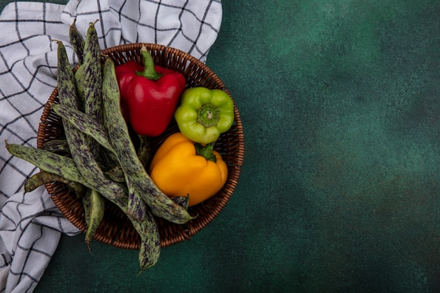 Top view  copy space green beans with bell peppers in a basket on a checkered towel  on a green background