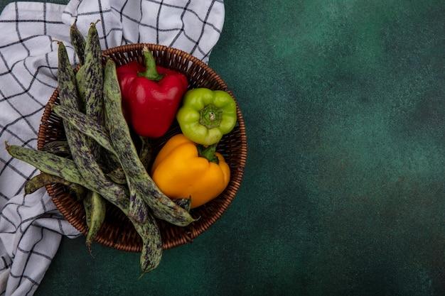 Вид сверху копией космической зеленой фасоли со сладким перцем в корзине на клетчатом полотенце на зеленом фоне