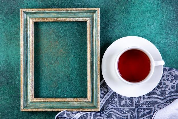 상위 뷰 복사 공간 그린 주방 타월에 차 한잔과 함께 그린 골드 프레임