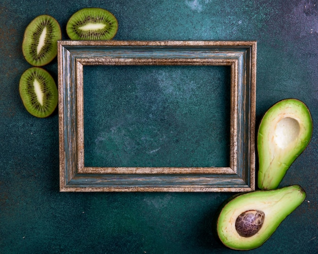 Top view copy space green-gold frame with avocado halves and kiwi slices on a dark green background