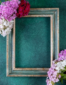 Top view copy space green-gold frame with colorful flowers on the edges on green
