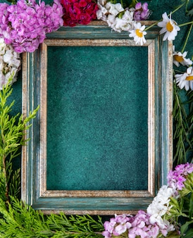 Top view copy space green-gold frame with fir branches and colorful flowers on the edges on green