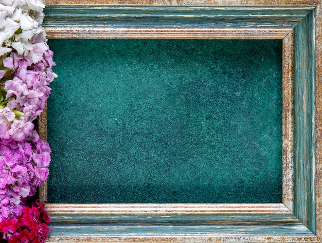 Top view copy space green-gold frame with pink red and white flowers from the side on green