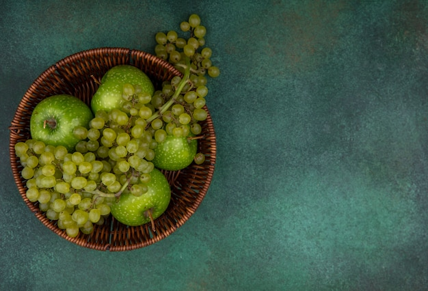 Вид сверху копией пространства зеленого винограда с яблоками в корзине на зеленом фоне