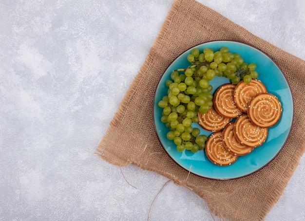 上面図コピースペース白い背景の上のベージュのナプキンの青いプレートにクッキーと緑のブドウ