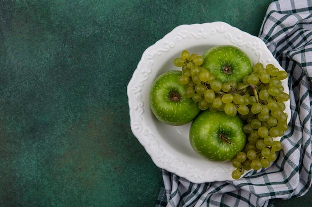 Вид сверху копией космического зеленого винограда с зелеными яблоками в тарелке с клетчатым полотенцем на зеленом фоне