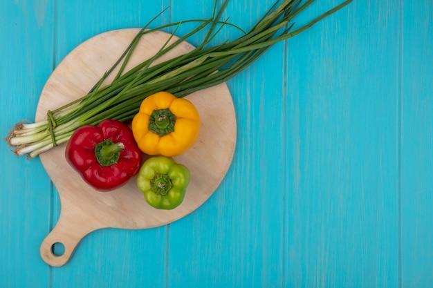 Вид сверху копией космического зеленого лука на разделочной доске с зеленым желтым и красным болгарским перцем на бирюзовом фоне
