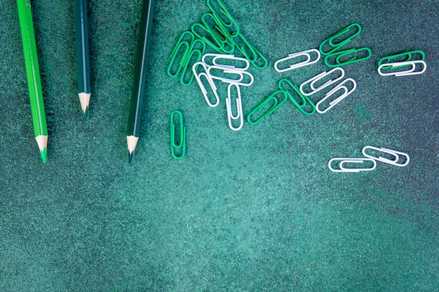 Top view copy space green pencils with green and white paper clips on a green background
