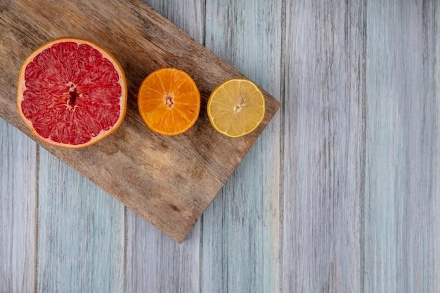灰色の背景のまな板に半分オレンジとレモンと上面コピースペース半分グレープフルーツ