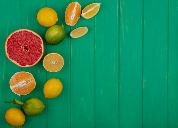 上面図コピースペース緑の背景に皮をむいたオレンジとレモンライムのスライスと半分のグレープフルーツ