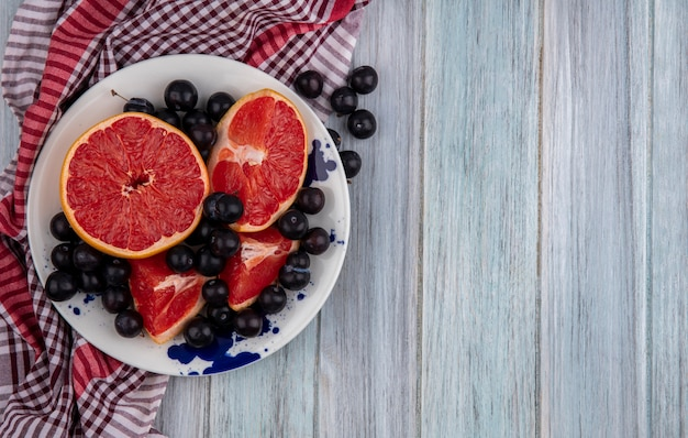Top view  copy space halved grapefruit with cherry plum on a plate  on a checkered towel  on a gray background