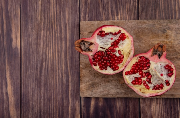 Top view copy space halved pomegranate on a cutting board on a wooden wall