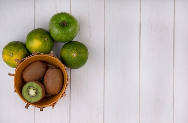 Merce nel carrello del kiwi dello spazio della copia di vista superiore con i mandarini e la mela verdi sulla parete bianca