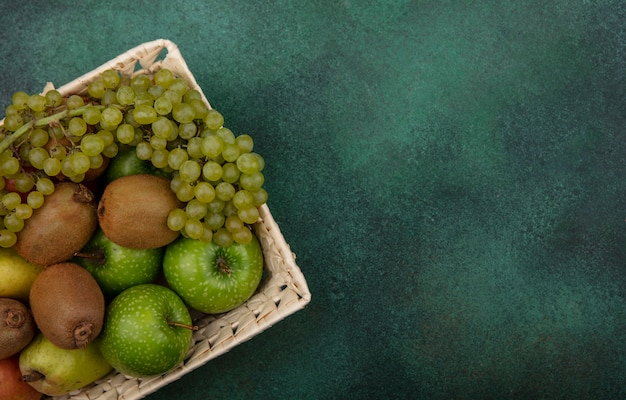 緑の背景にバスケットに青リンゴブドウと梨とトップビューコピースペースキウイ