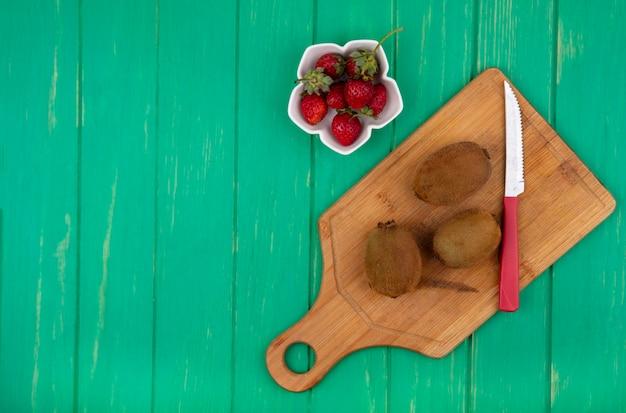 Vista dall'alto lo spazio della copia kiwi con un coltello su un tagliere e fragole su una parete verde