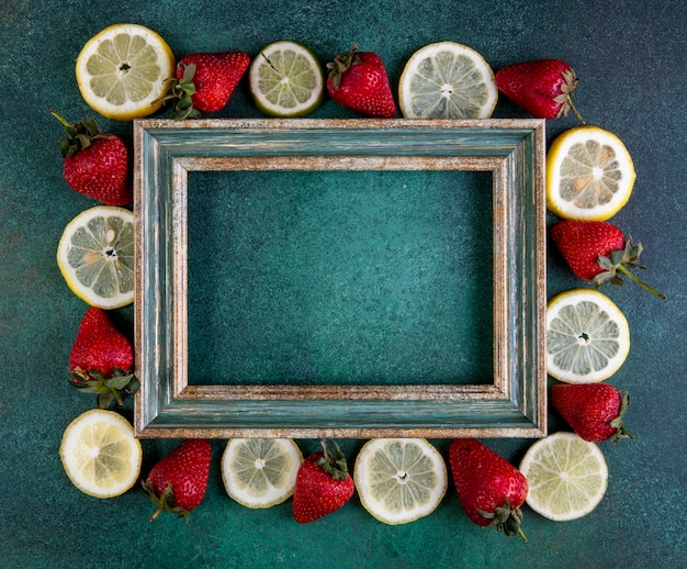 Top view  copy space lemon slices and lime with strawberries around the frame on a green background