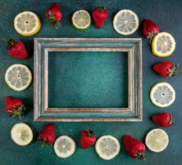 Top view copy space lemon slices and lime with strawberries around the frame on green