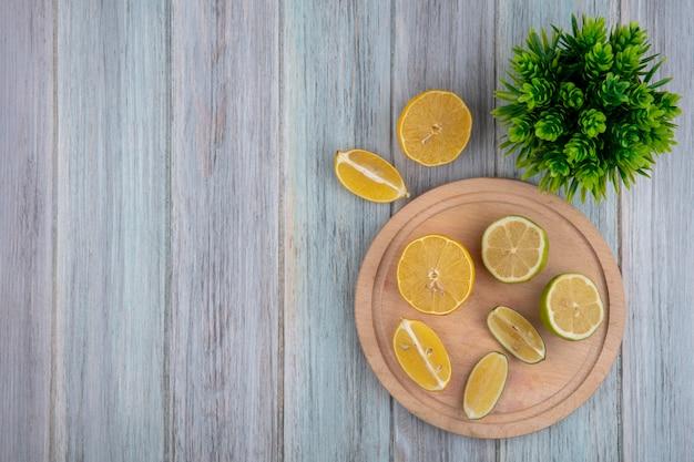Вид сверху копией пространства дольками лимона с лаймом на разделочной доске на сером фоне