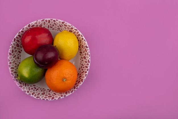 Вид сверху копия космического лимона с лаймом, персиком, сливой и апельсином в тарелке на розовом фоне