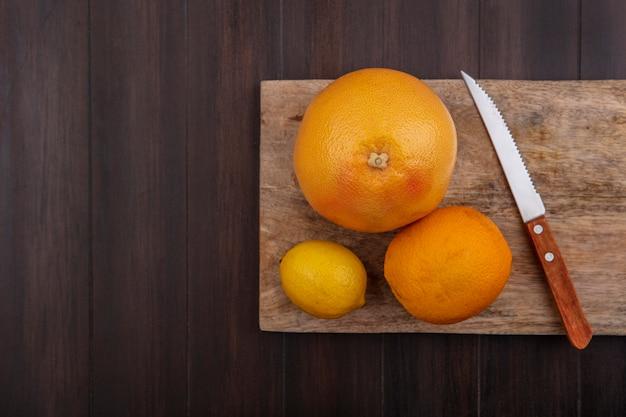 木の背景にナイフでまな板にオレンジとグレープフルーツとレモン