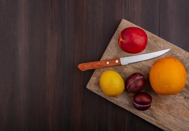 Вид сверху копией космического лимона с апельсином и персиком со сливой на разделочной доске с ножом на деревянном фоне
