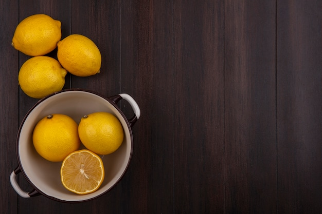 Top view  copy space lemons in white saucepan on wooden background