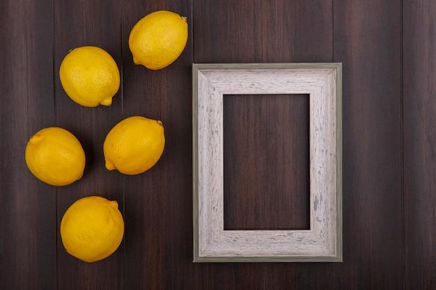 나무 배경에 회색 프레임 상위 뷰 복사 공간 레몬