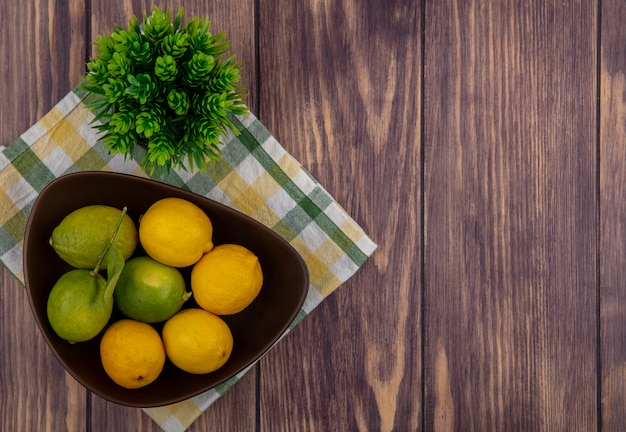 Top view  copy space lemons with limes in a bowl on a yellow-green checkered towel  on a wooden background