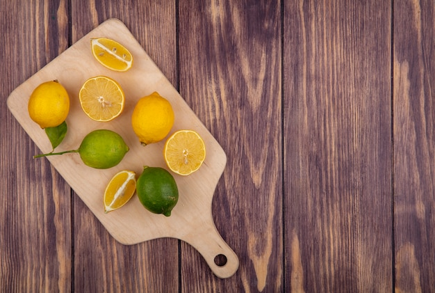 Top view  copy space lemons with limes on a cutting board on a wooden background