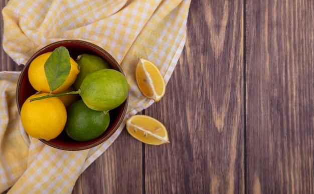 Вид сверху копией космических лимонов с лаймами в миске на желтом клетчатом полотенце на деревянном фоне