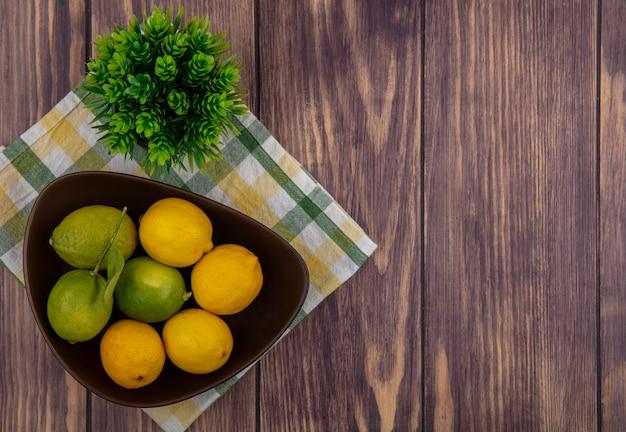 木製の背景に黄緑色の市松模様のタオルの上のボウルにライムとスペースレモンをコピーして上面図