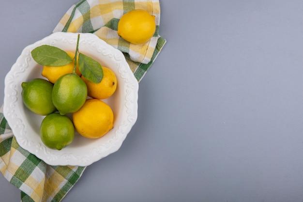 Вид сверху копией космических лимонов с лаймами в тарелке на желтом клетчатом полотенце на сером фоне