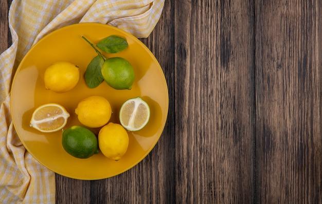 上面図コピースペースレモンとライム、黄色のプレートに黄色の市松模様のタオルと木製の背景