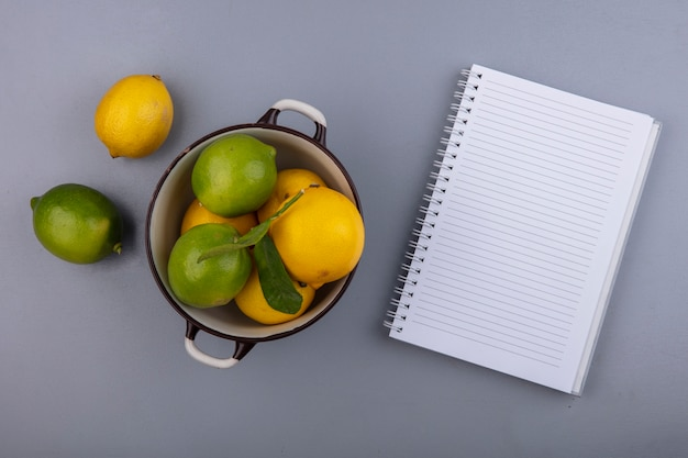 Limoni di spazio copia vista dall'alto con limette in una casseruola con blocco note su sfondo grigio