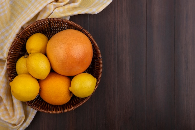 Top view  copy space lemons with orange and grapefruit in basket with yellow checkered towel on wooden background
